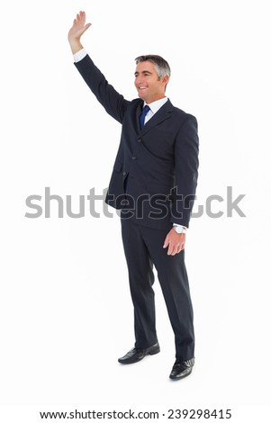 Smiling businessman in suit waving on white background - stock photo