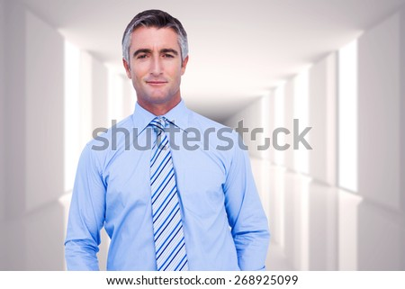 Smiling businessman in suit with hands in pocket posing against digitally generated room