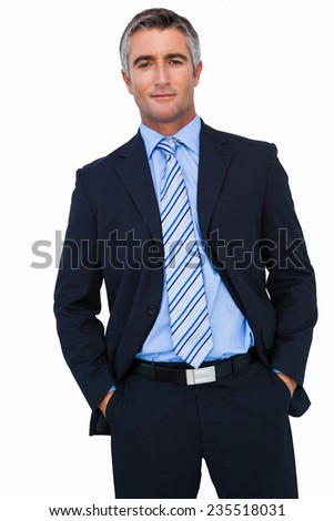 Smiling businessman in suit with hands in pocket posing on white background