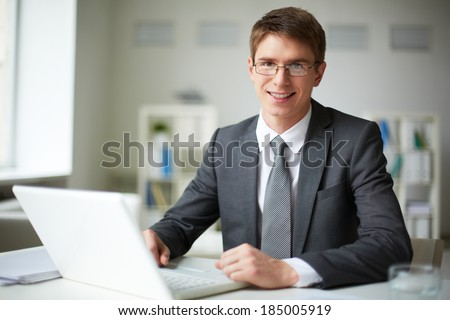 Smiling businessman in suit working with laptop in office - stock photo