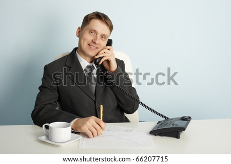 Smiling businessman in talks on the phone in the office