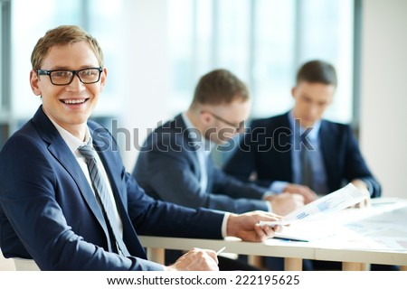 Smiling businessman in the background of his working colleagues - stock photo