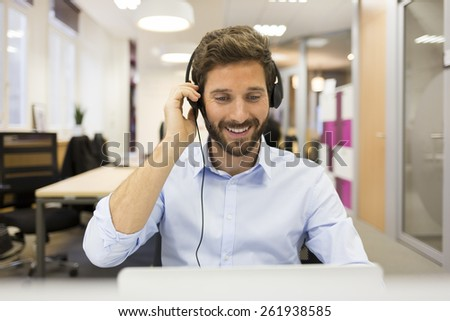 Smiling Businessman in the office on video conference, headset  - stock photo