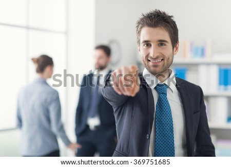 Smiling businessman in the office pointing at camera, recruitment and selection concept - stock photo