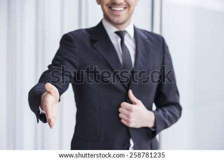 Smiling businessman is wearing in suit, handshake to you. - stock photo