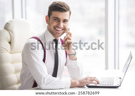 Smiling  businessman is working on his laptop in his office and is speaking phone and looking at camera. - stock photo