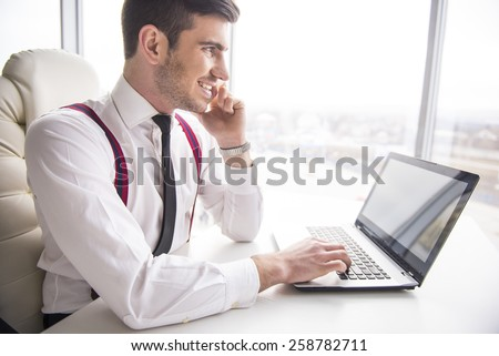 Smiling  businessman is working on his laptop in his office and is speaking phone and looking away. - stock photo
