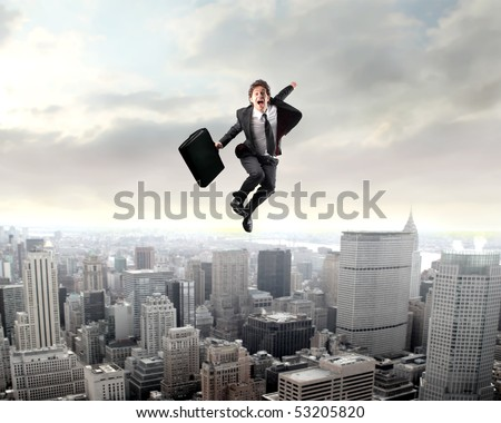 Smiling businessman jumping with cityscape on the background - stock photo