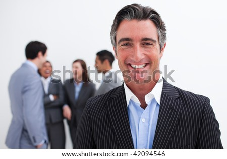 Smiling businessman leading her team agaisnt white background - stock photo