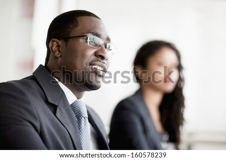 Smiling businessman listening at business meeting - stock photo