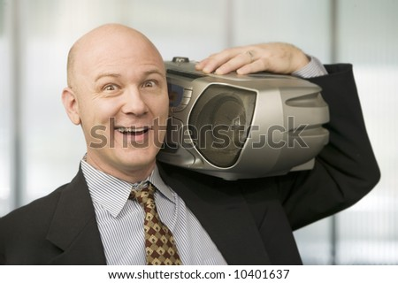 Smiling Businessman listening to a big Boom Box - stock photo