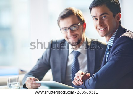 Smiling businessman looking at camera with his colleague on background