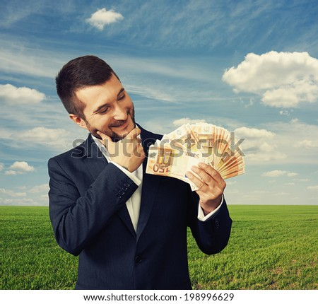 Smiling businessman looking at money and thinking about something, outdoors. - stock photo