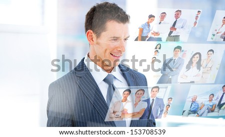 Smiling businessman looking at pictures on digital screen - stock photo