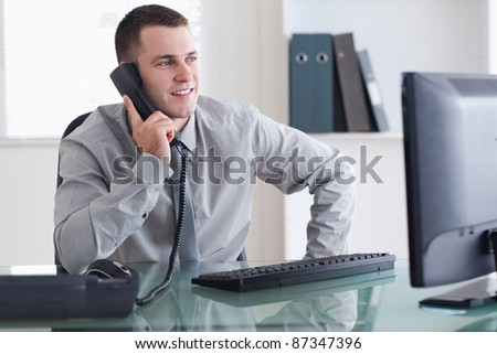 Smiling businessman looking at the screen while on the phone - stock photo