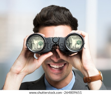 Smiling businessman looking to dollar banknotes through binoculars - stock photo
