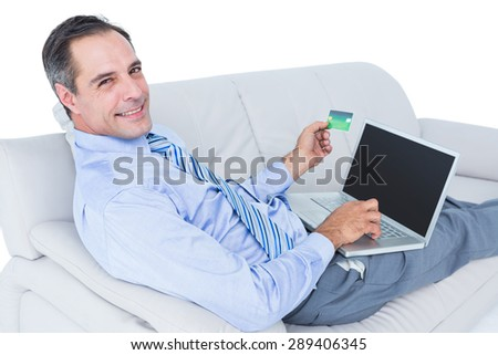 Smiling businessman lying ona sofa holding a card and laptop against a white wall - stock photo