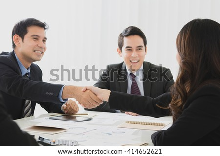 Smiling businessman making handshake with a businesswoman in the meeting - stock photo