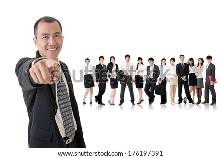Smiling businessman of Asian point at you and standing in front of his team on studio white background.