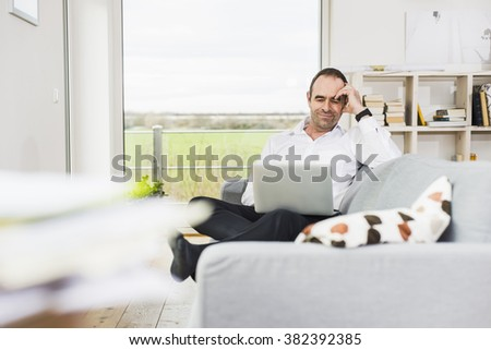 Smiling businessman on couch using laptop