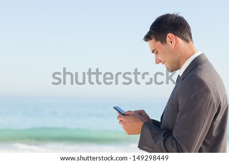 Smiling businessman  on the beach sending a text message - stock photo