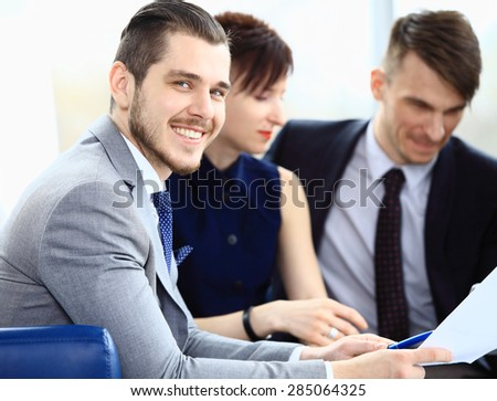 Smiling businessman on the foreground and his coworkers discussing business