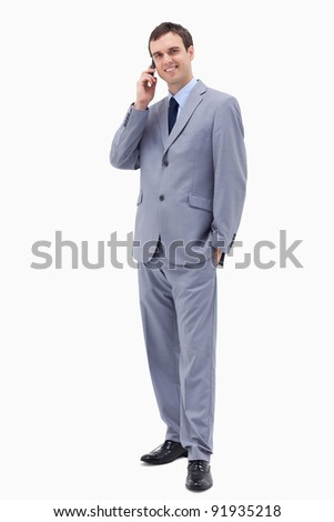Smiling businessman on the phone against a white background - stock photo