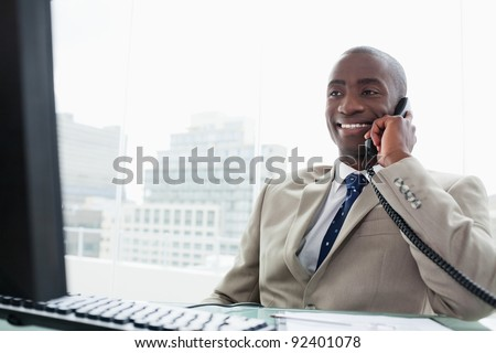 Smiling businessman on the phone in his office - stock photo