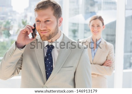 Smiling businessman on the phone with partner standing behind