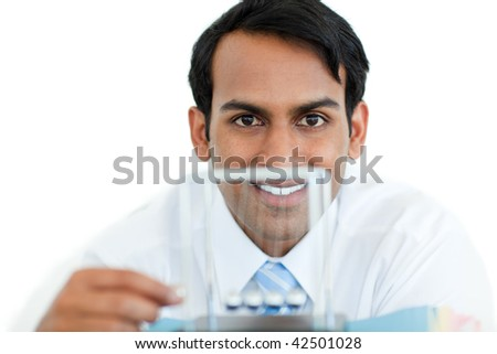 Smiling businessman playing with kinetic balls at work - stock photo