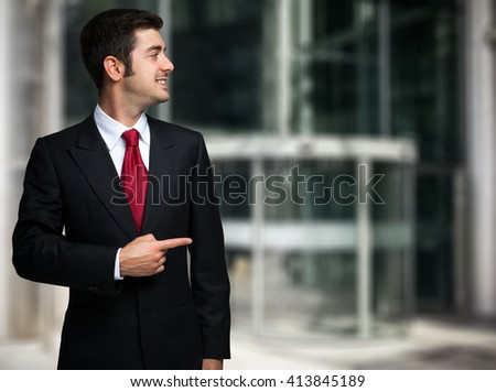 Smiling businessman pointing his finger to the copyspace - stock photo