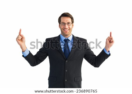 Smiling businessman pointing with both fingers on white background - stock photo