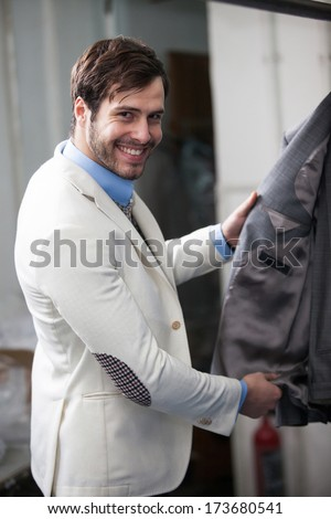 Smiling businessman portrait, elegant and classic, wearing white coat shopping for clothes at the store. - stock photo