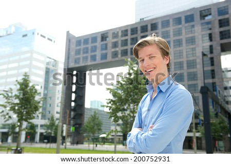 Smiling businessman posing with arms crossed outside city building