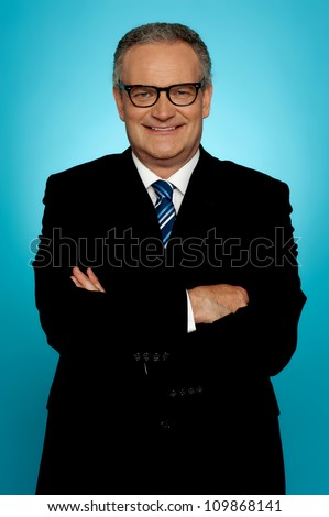 Smiling businessman posing with crossed arms looking at you - stock photo