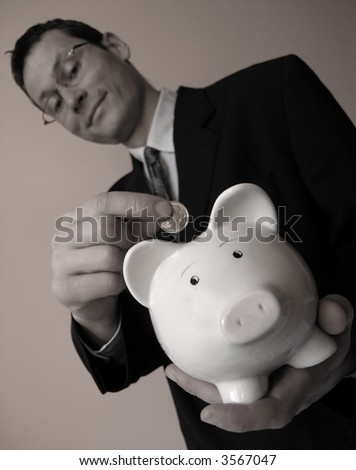 Smiling businessman puts coin in a piggy bank. - stock photo