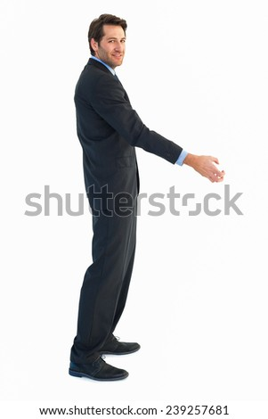 Smiling businessman reaching out to shake hands on white background - stock photo