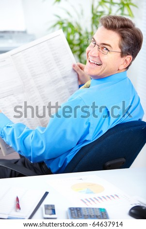 Smiling businessman reading newspaper in the office