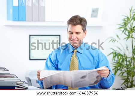 Smiling businessman reading newspaper in the office - stock photo