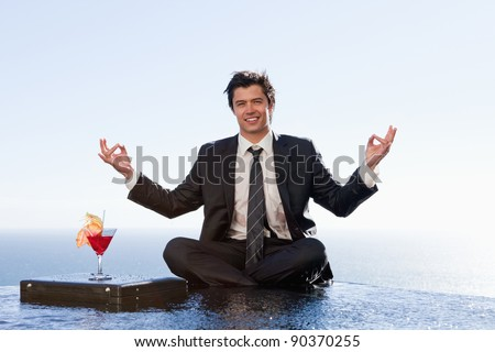 Smiling businessman relaxing in the lotus position with a cocktail in a swimming pool - stock photo