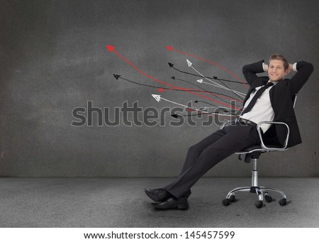 Smiling businessman resting in a chair and looking at camera with arrows on the wall - stock photo