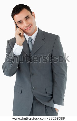 Smiling businessman ringing someone against a white background