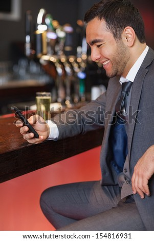 Smiling businessman sending a text while having a drink in a classy bar - stock photo