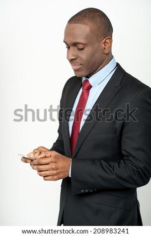 Smiling businessman sending message using mobile phone - stock photo