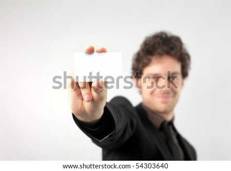 Smiling businessman showing a card - stock photo