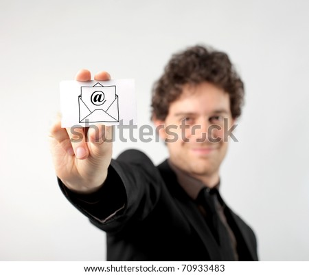 Smiling businessman showing a card with an e-mail sign on it - stock photo