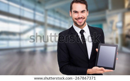 Smiling businessman showing his tablet pc against fitness studio - stock photo