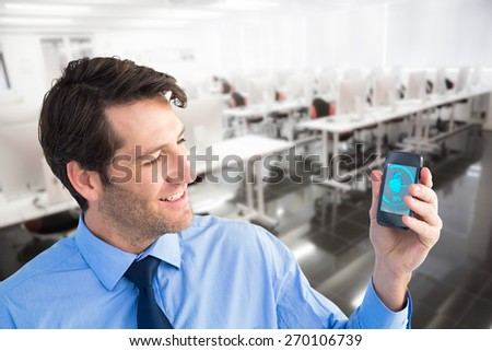 Smiling businessman showing smartphone to camera against empty computer room - stock photo