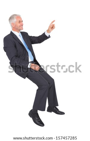 Smiling businessman sitting and pointing finger on white background