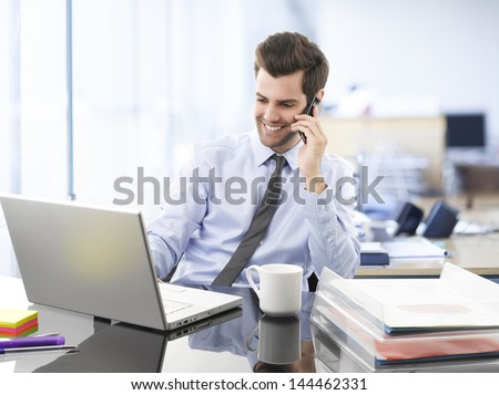 Smiling businessman sitting and using mobile phone in office - stock photo
